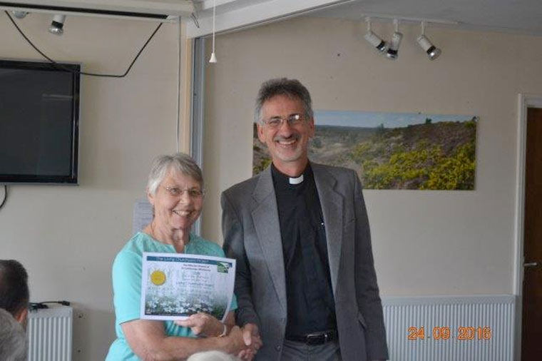 Margaret Turner who leads the small group that cares for God's Acre receiving the gold award from the Archdeacon of Dorset, the Venerable Antony Macrow-Wood