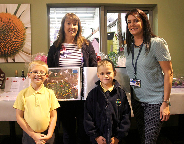 Ferndown First pupils Harry and Tyler with teaching assistant Mrs Maylin (holding book) and teacher Miss Ware