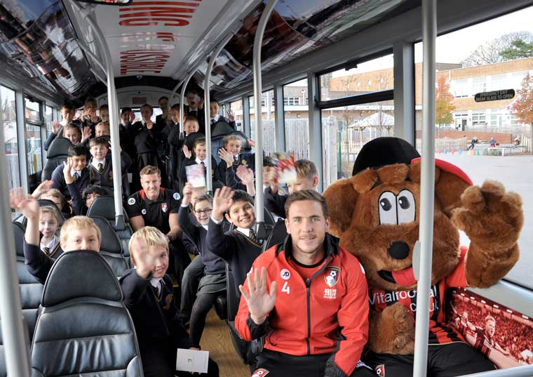 Steve Fletcher (centre) with Dan Gosling and Cherry Bear plus children from King's Park Academy on the Cherries-themed bus