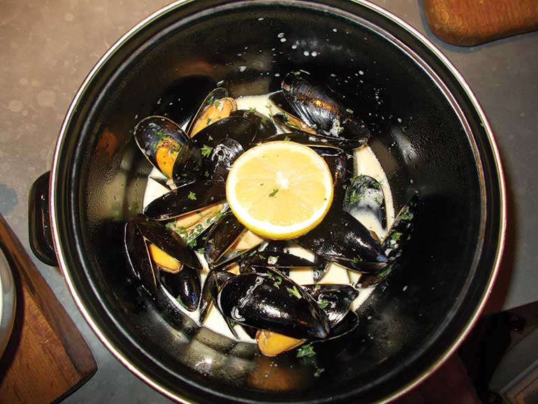 Moules frites or mussels served in a cream and white wine sauce