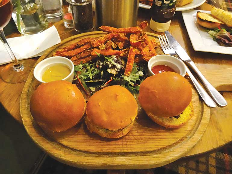 Trio of mini burgers - beef with bacon and cheese, pork and apple and minted lamb burgers in brioche buns with sweet potato fries, mustard and ketchup