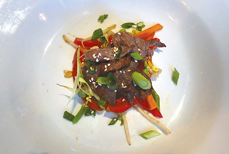 Asian beef salad with strips of beef marinated in soy, served with peanuts, chilli bok choi and beansprouts