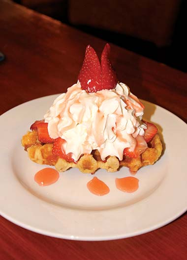 Belgian waffle with ice cream, strawberries and strawberry sauce