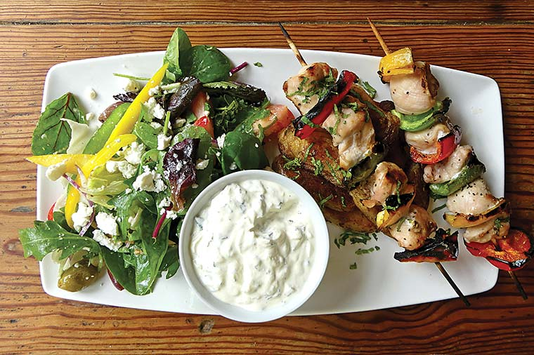 Chicken kebabs with Cajun-fried potatoes, tzatziki and Greek salad