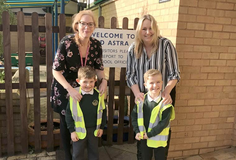 Children wearing high-vis jackets donated by Meridian Lifts. (L to R) Joanne Tomlin, owner, Meridian Lifts with Lucy Waterhouse, head of school, Ad Astra Infant School with children Max Simpson and Joshua Neville
