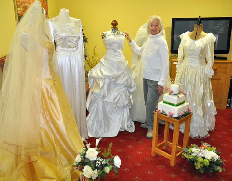 Newstone House resident Catherine Matthews poses with some of the wedding dresses