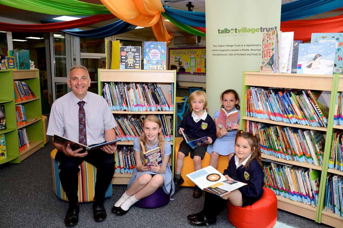 Headteacher, Richard Gower, and pupils enjoy the new library at Kingsleigh Primary School.