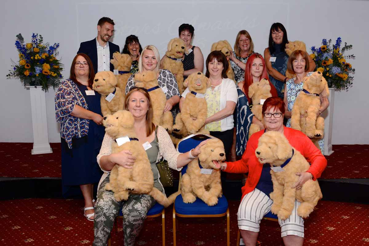 What a lot of Biscuits! Care South home managers with their robotic therapy dogs