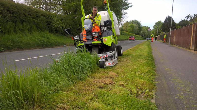 Cutting the verge on a roadside in Dorset