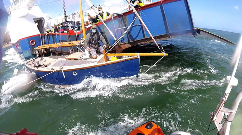 Stricken vessel pinned against the chain ferry © RNLI Poole