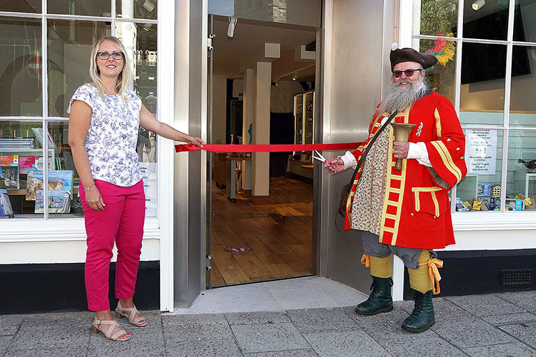 Town crier, Chris Brown cuts the ribbon in the presence of Lindsay Lawrence, Business and Visitor Services manager