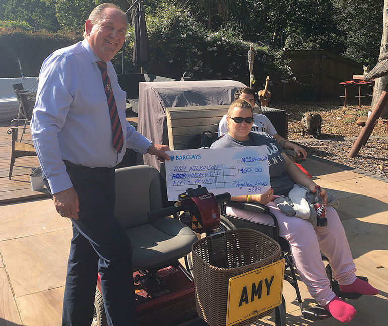 Chris Lockwood from the Freemasons presenting Amy with a mobility scooter and a cheque