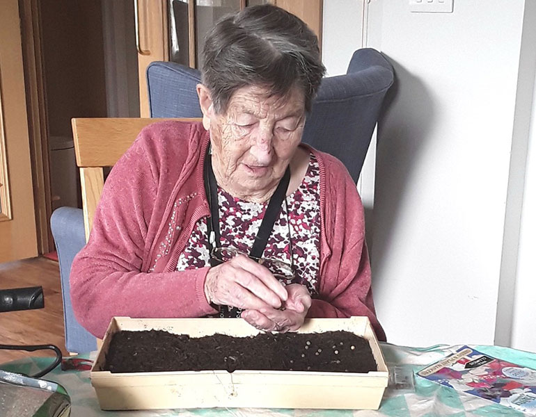 Doris, a member of the gardening club at Avon Reach in Mudeford, planting seeds for the show