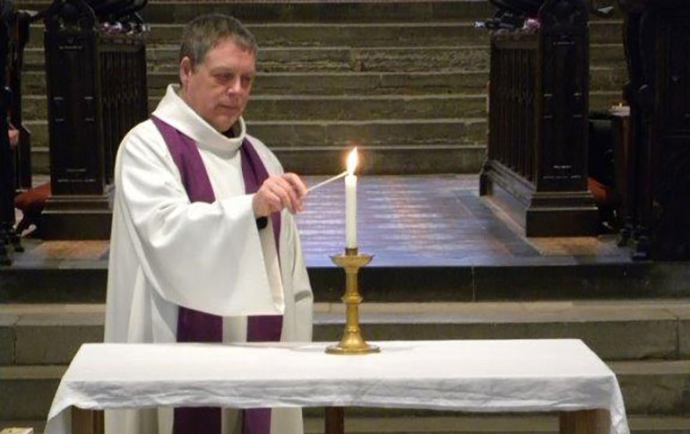 The Rev Canon Andrew Rowland lights a candle
