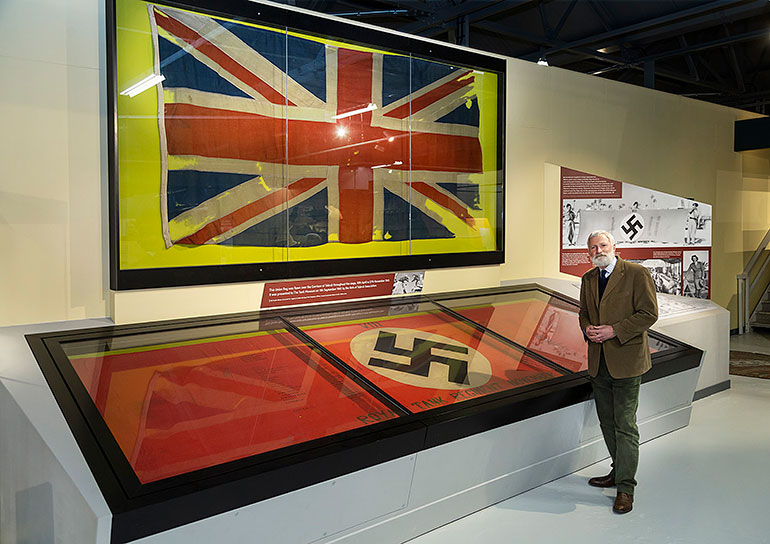 David Willey, curator of The Tank Museum, with the two flags