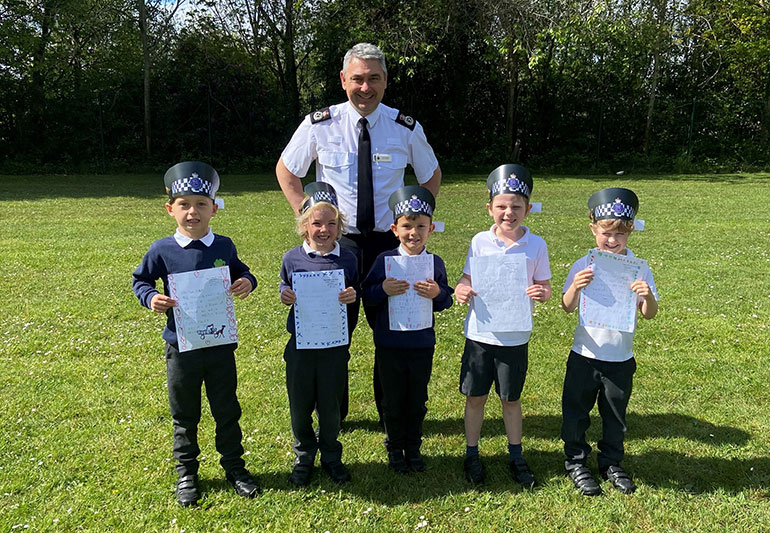 Chief Constable James Vaughan and the five children who wrote to him L-R Harry, Dexter, Nathan, Alfie and Fred