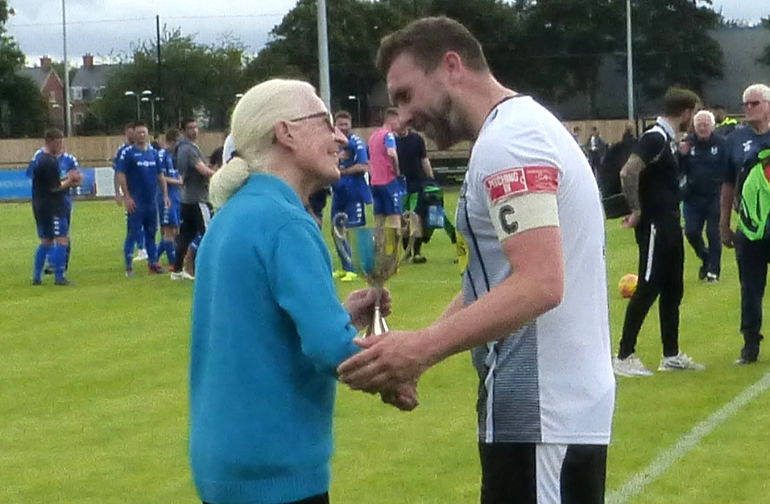 Gerry Page's widow, Dawn, presents the trophy to Wimborne's Club Captain Scott Arnold