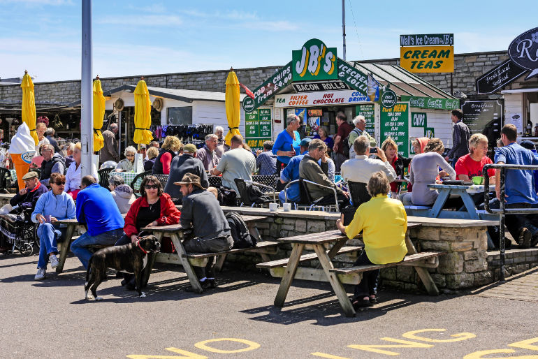 People sitting at picnic tables in West Bay