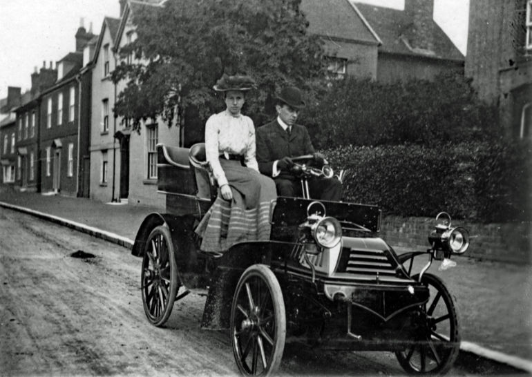 Ernest Kaye Le Fleming with his wife, Florence, in their first car outside Gordon House in 1902. Vehicle registration plates were introduced in 1903