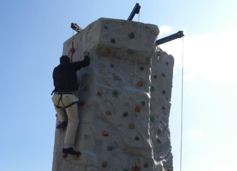 The rector nears the top of the climbing wall in a fundraising event for the church. Picture by Anthony Oliver